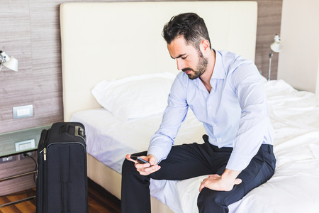 Businessman looking at smart phone in his hotel room. He is sitting on the bed, wearing black trousers and a light blue shirt. Grave expression, business and work issues concepts.