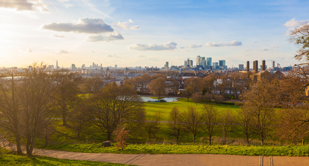 greenwich: Panoramic view of London from Greenwich park at sunset. Many famous buildings and skyscrapers of the city are easily recognisable on background.
