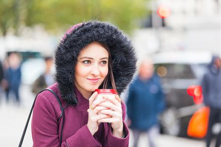 soledad: Mujer joven hermosa al lado de una carretera muy transitada que sostiene una cuf de té. Foto tomada en Londres, con la gente y el tráfico en el fondo. Ella lleva ropa de abrigo. Estilo de vida y soledad conceptos. Foto de archivo