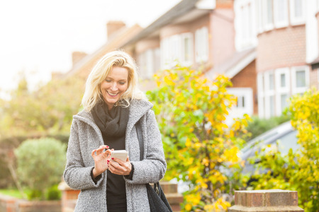 early forties: Adult woman looking at smart phone in front of some houses in London. She is a blonde woman on her early forties, she looks candid and spontaneous. Lifestyle and technology concepts.