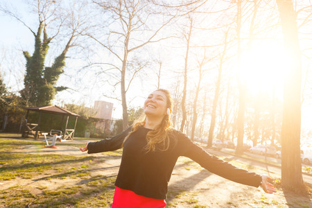 looking away from camera: Young woman stretching after workout at park. She is standing with outstretched arms, smiling and looking away from camera. She looks relaxed, satisfied and happy. Sport and healthy lifestyle concepts