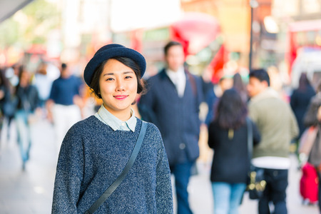blurred people: Portrait of an asian young woman with blurred people on background in a busy street of London. She is wearing a hat and looking at camera smiling. Lifestyle and travel concepts. Stock Photo
