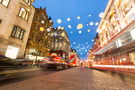 Oxford street in London with Christmas lights and blurred traffic. It is one of the busiest street of the capital city of England, and during Christmas time it becomes magic and fairy. Archivio Fotografico