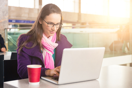 mid twenties: Young woman working with computer in a train station or airport. She is in her mid twenties,wearing a coat, a scarf and eyeglasses and she is typing on the keyboard.