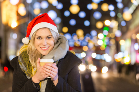 christmas tea: Beautiful young woman wearing Santa hat in London. She is blonde, on her early twenties, holding a cup of coffee and wearing warm clothes. On background there are many Christmas lights.