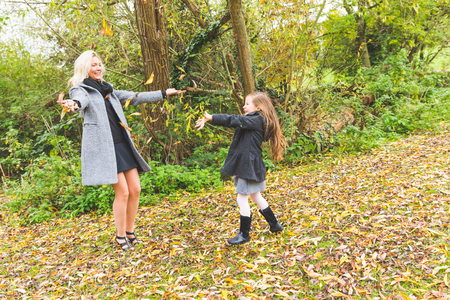 playful: Mother and daughter playing with leaves at park in autumn. The mother is caucasian, the girl is mixed race daughter, they are looking each other and throwing leaves. Family lifestyle concept. Stock Photo