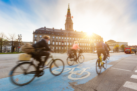 Blurred people going by bike in Copenhagen, with Christiansborg palace on background. Many persons prefer biking instead of taking car or bus to move around the city. Urban lifestyle concept. Publikacyjne