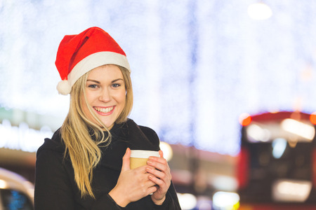 early twenties: Beautiful young woman wearing Santa hat in London. She is blonde, on her early twenties, holding a cup of coffee and wearing warm clothes. On background there are many Christmas lights