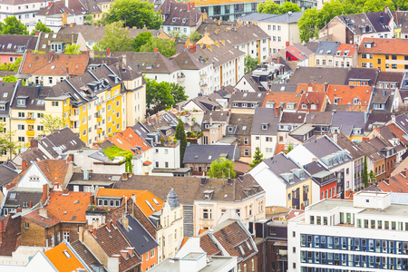 not painted: Aerial view of houses and rooftops in Cologne, Germany. Many of them are colourful, some are older and not painted. There are some trees in the gardens. Central Europe architecture.