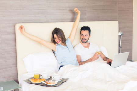 A man and a woman are having breakfast on the bed. They are drinking coffee and juice and eating croissants. They are enjoying relax on holiday but they are also working with computer. Stockfoto