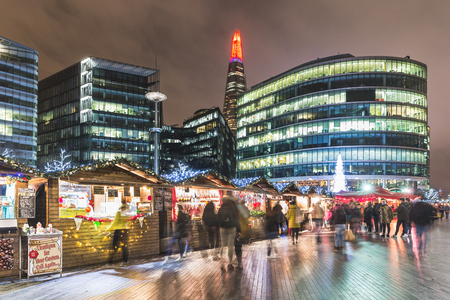 market hall: LONDON, UK - DECEMBER 12, 2015: Night view of London Bridge City Christmas Market with blurred people walking and shopping, long exposure shot. On background there are some famous skyscrapers.