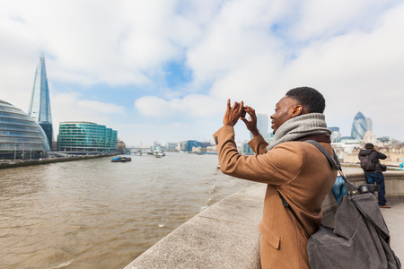 jamaican adult: Man taking a picture in London with his smart phone. He is on the Tower Bridge, looking at cityscape. Photo taken on a cloudy winter day.