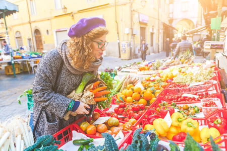 Vegetarian vegan young woman buying vegetables at local market. She is looking at some tomatoes, holding carrots on her harms. Sustainable cultivation concept.
