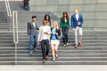 young professionals: Business multiracial group walking down a staircase in London. They all are young, smiling and wearing smart casual clothes. Mixed race group. Teamwork and business concepts.