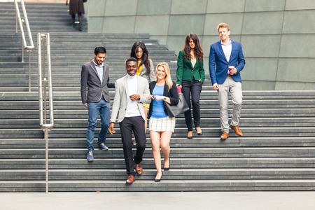 profesionistas: Unidad de negocio multirracial caminando por una escalera en Londres. Todos ellos son jóvenes, sonriente y con ropa casual elegante. grupo de raza mixta. Trabajo en equipo y de negocios conceptos.