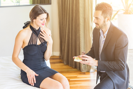 Love couple with man asking her girlfriend to get married with a ring on Valentines day. They are both wearing elegant clothes, he is going down on one knee in front of her. photo