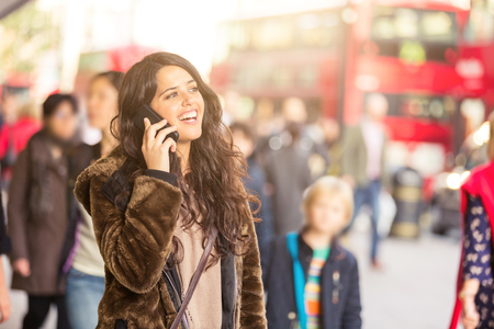 spanish woman: Spanish woman talking on the phone with blurred people on background in a busy street of London. She is wearing a fur and looking away from camera. Lifestyle and travel concepts. Stock Photo