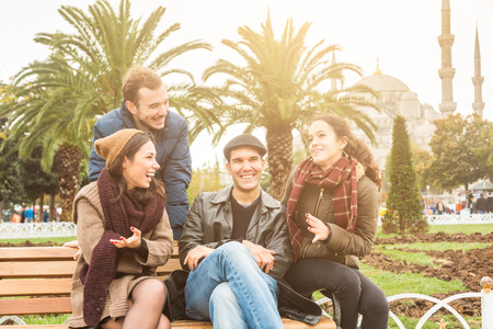 turkish people: Group of Turkish friends in Istanbul. They are two men and two women, sitting on a bench at park with a mosque on background. They are wearing warm clothes. Travel and lifestyle concepts.