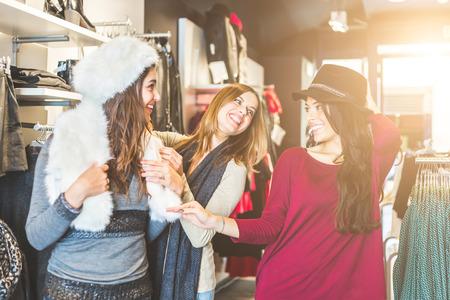 chicas de compras: Tres mujeres en un tiempo de compras tienda de ropa disfrutando. Ellos están tratando algunos sombreros, mirando el uno al otro sonriendo y riendo. Amistad, el estilo de vida y el consumo conceptos.