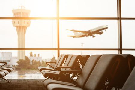 Sillas vacías en la sala de embarque en el aeropuerto, con la torre de control y un avión despegando al atardecer. Viajes y transporte conceptos.