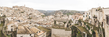 origins: Panoramic view of old town in Matera, capital city of Basilicata county in Italy. It is famous worldwide for its sassi, typical houses and with prehistorical origins. Architecture and travel concepts.