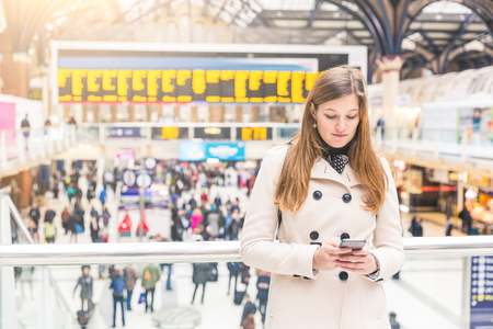 citylife: Young woman typing on her smart phone at train station. She is on her mid twenties, alone, looking at the phone while waiting for a train or for a friend. Travel and lifestyle concepts. Stock Photo