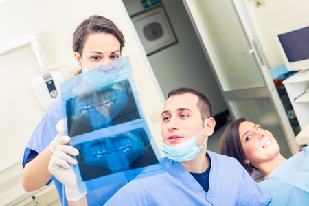 Dentist and dental assistant examining an X-ray image of patient mouth. They are young adults, with cheerful expressions, trying to create a relaxed experience for the patient. Medical and healthcare photo