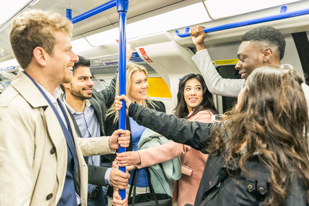 strangers: Group of people on tube train in London. They are a mixed group of persons, wearing smart casual clothes. They could be friends or just strangers. Urban lifestyle and transportation concepts. Stock Photo