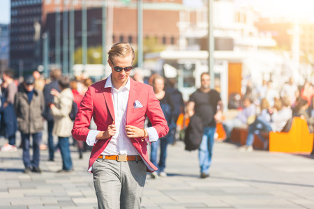 facial features: Fashioned young man in Oslo walking on crowded sidewalk with people on background. He has nordic facial features, and wearing a red jacket with gray trousers Stock Photo