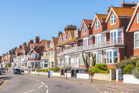 전형적인 집들이있는 잉글랜드 남부의 거리. 옆에 전형적인 영국 주택이있는 마을에 메인 스트리트가 있습니다. 그들은 전면에 벽과 작은 문이있는 빨