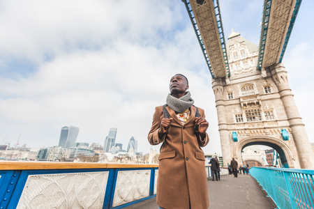 jamaican adult: Young black man standing on Tower Bridge with London skyline  on background. He wears a brown coat and he is looking away from camera.
