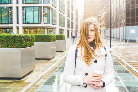 tousled: Portrait of a beautiful woman in London with hair tousled by the wind. She is on her mid twenties, wearing a light grey coat and holding a coffee cup. Waist up view. Stock Photo