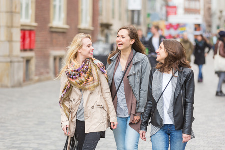 three persons only: Group of women walking in Copenhagen. They are in their twenties and they are wearing smart casual clothes. Happiness and friendship concepts, they are smiling and looking each other.