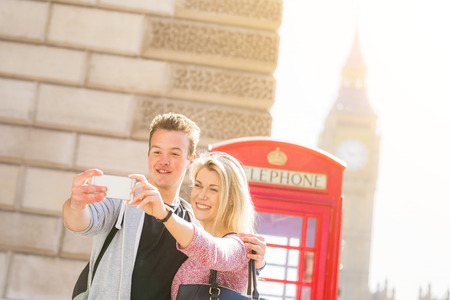 cabina telefono: Londres, feliz pareja joven que toma una autofoto con una cabina de teléfono roja y el Big Ben en el fondo. Ellos están de vacaciones para el día de San Valentín o que están disfrutando de su luna de miel. Foto de archivo