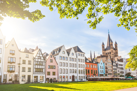 residential neighborhood: Houses and park in Cologne, Germany. Many of them are colourful, they are facing a public park with green grass and some trees. There is a bell tower on background. Travel and architecture concepts. Editorial