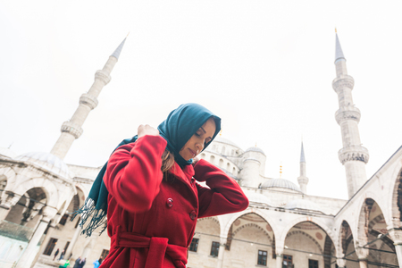 mid twenties: Young Arabian woman wearing veil in front of a mosque in Istanbul. She is in her mid twenties, wearing a red coat on a rainy day. On background there are the mosque and the minarets.