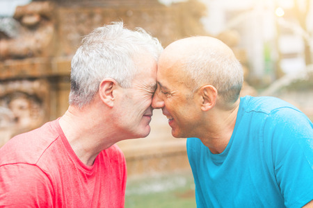 smuggling: Gay couple at park in New York. They are two men in their early sixties, standing face to face, cuddling and smuggling. Homosexual love concept