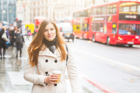 mid twenties: London, young business woman walking along the road with traffic and red buses on background. She is on her mid twenties, alone, looking in front of her and holding a cup of coffee.