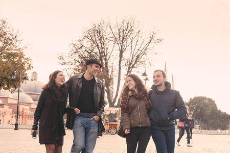 mid twenties: Istanbul, group of friends walking in Sultanahmet square. They are two men and two women in their mid twenties, talking and laughing while looking each other. Friendship and lifestyle concepts
