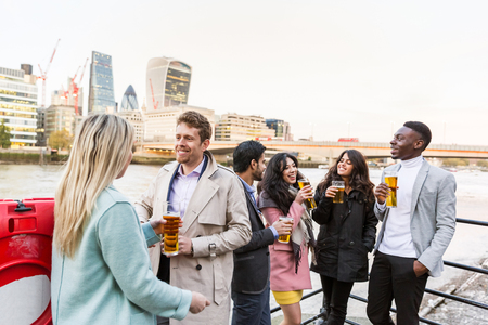 young adult women: Business group in London drinking beer after work. They all are young, smiling and wearing smart casual clothes. Mixed race group. Also could refer to a group of friends.