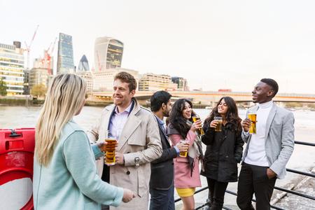 jovenes tomando alcohol: Unidad de negocio en Londres beber cerveza después del trabajo. Todos ellos son jóvenes, sonriente y con ropa casual elegante. grupo de raza mixta. También podría referirse a un grupo de amigos.