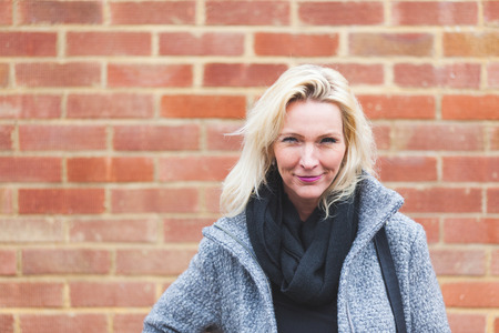 self confident: Portrait of a beautiful blonde woman posing against a brick wall. She is looking at camera and smiling. She wears a coat and a scarf. Determination and self confidence concepts.