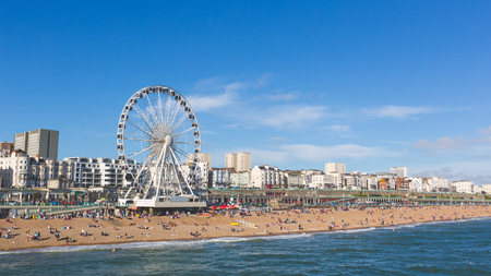 panoramic beach: Brighton view of seaside from the pier. Panoramic shot with the famous ferris wheel, the stones beach with unrecognizable persons on a sunny summer day.