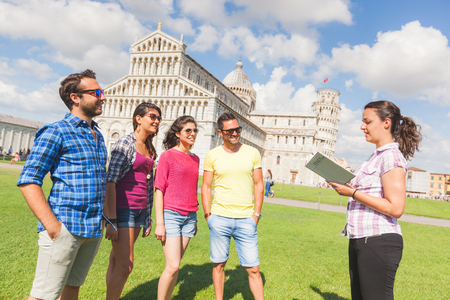 guide: Group of tourists in Pisa, Italy. A group of friends is listening to a guide talking about a famous monument. They are two women and two men wearing summer clothes. They are a multicultural group on holidays.