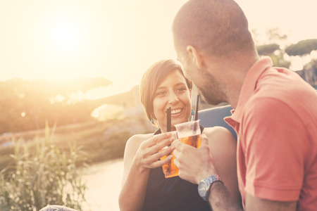 Couple having a cocktail and toasting outdoor on summer. The bar is next to a river, backlight scene at sunset. They are looking each other, the man is showing his shoulders to the camera. photo