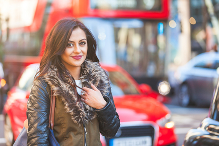 Indian girl portrait in London. She is standing by a busy road with blurred traffic on background. There are cars and red buses. She is smiling and looking at camera. Travel and lifestyle concepts Imagens