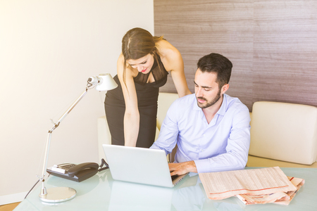 Business situation with boss and secretary. The man is sitting at table and wearing a light blue shirt, the woman wears an elegant black dress. There is a financial newspaper on the desk. photo