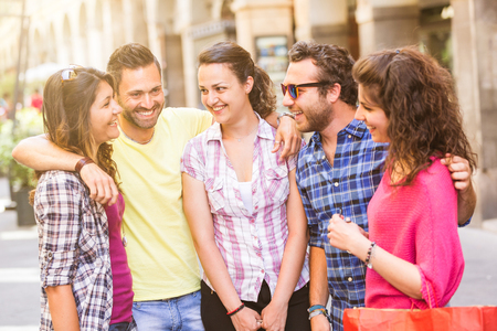 Group of friends meeting in the city. They are young and happy, and they could be tourists or students. The photo was taken in Pisa, Italy, but could also be used for Rome, Florence or Milan. photo
