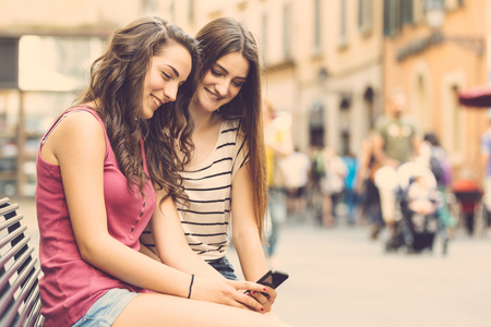 benches: Two girls looking at a smartphone and sitting on a bench. They are two teen girls on a sunny summer day. Friendship, technologies and lifestyle concepts. Stock Photo