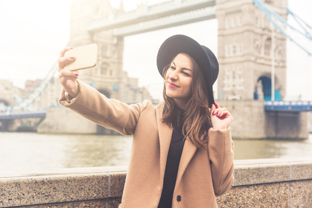 Fashionable girl taking a selfie in London with Tower Bridge on background. She is wearing a camel coat and black hat and grimacing to the camera. Vintage filter applied. Stock Photo
